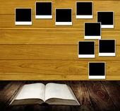 Lezen van boek met foto frames post op houten muur, lezen tafelconcept — Stockfoto