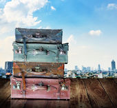 Vintage travel luggage on wooden wall with city view background — Stock Photo