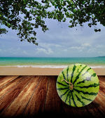 Watermelon on wooden deck with beach in summer time — Stock Photo