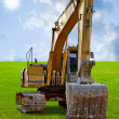 Track-type loader excavator machine on green grass field — ストック写真