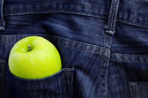 Green apple in Jeans pocket — Stock Photo