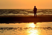 Silhouette man on beach with sunset sky background — Stock Photo
