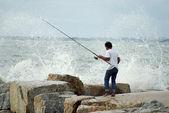 CHONBURI, THAILAND - JULY 25 : Unidentified man fishing with big wave splashing on 15 April 2011 in Sriracha beach, Chonburi, Thailand  — Stock Photo