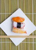Sushi nigiri in with dish with bamboo sticks — Stock Photo