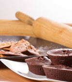 Chocolate muffin with cookies and kitchen tools on yellow background. — Stock Photo