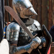 Knight in armour with shield and sword - Stock Photo