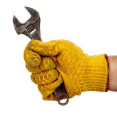 Adjustable wrench in hand with glove — Stock Photo