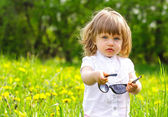 Little girl in a meadow with sunglasses — Stock Photo