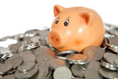 Piggy bank on pile of coins — Stockfoto