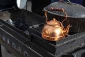 Old bronze teapot on black grill — Stok fotoğraf