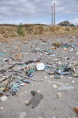 Trash on the seashore next to a factory — Stock Photo