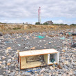 Stock Photo: Trashed fridge on seashore next to factory