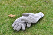 Dirty gardening gloves on the grass — Stock Photo