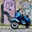 Blue scooter in front of a red brick wall — Foto Stock
