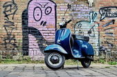 Blue scooter in front of a red brick wall — Stock Photo