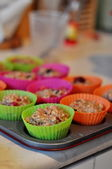 Cooking muffins in colourful plastic cups — Stock Photo