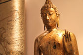 Golden Buddha statue lit atmospherically — Stock Photo