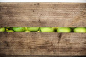 Green apple in a wooden box — Stock Photo
