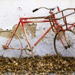 Decorative old bicycle against an old peeling wall — Stock Photo