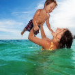 Mother play with her son in the sea — Stock Photo