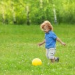 Little boy kicking yellow ball — Stock Photo