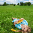 Smiling girl laying on lawn — Stock Photo