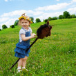 Happy girl with horse stick — Stock Photo