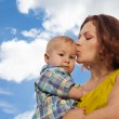 Mother kissing her baby on cloudy background — Stock Photo