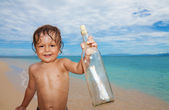 Kid found sos bottle in the sea — Stock Photo
