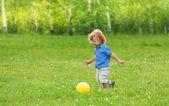 Little boy kicking yellow ball — Stock Photo