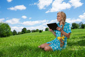 Student sitting on grass browsing — Stock Photo