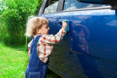 Cute kid washing parents car — Stock Photo
