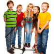 Foto Stock: Group of kids singing to microphone
