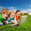 Excited kids with laptop in park — Stock Photo