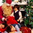 Kid looking for presents in Santa's bag with presents — Stock Photo #16295089