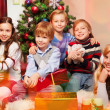 Cute kids sitting near Christmas tree — Stock fotografie