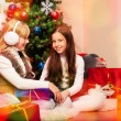 Two lovely girls under Christmas tree — Stok fotoğraf