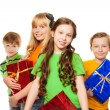 Stock Photo: Girls and boys holding presents