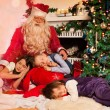 Santa Claus and sleeping kids — Stock Photo