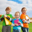 Three kids with books in park — Stock Photo