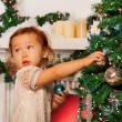 Little girl decorating Christmas tree — Stok fotoğraf