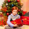 Cute boy sitting near Christmas tree — Stock Photo