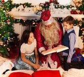 Santa leggendo il libro di Natale per i bambini — Foto Stock