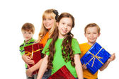 Girls and boys holding presents — Stock Photo
