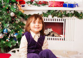 Five year old boy sitting by Christmas tree — Стоковое фото