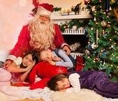 Santa claus en slapende jonge geitjes — Stockfoto