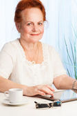 Smiling old woman with tablet pc — Stock Photo