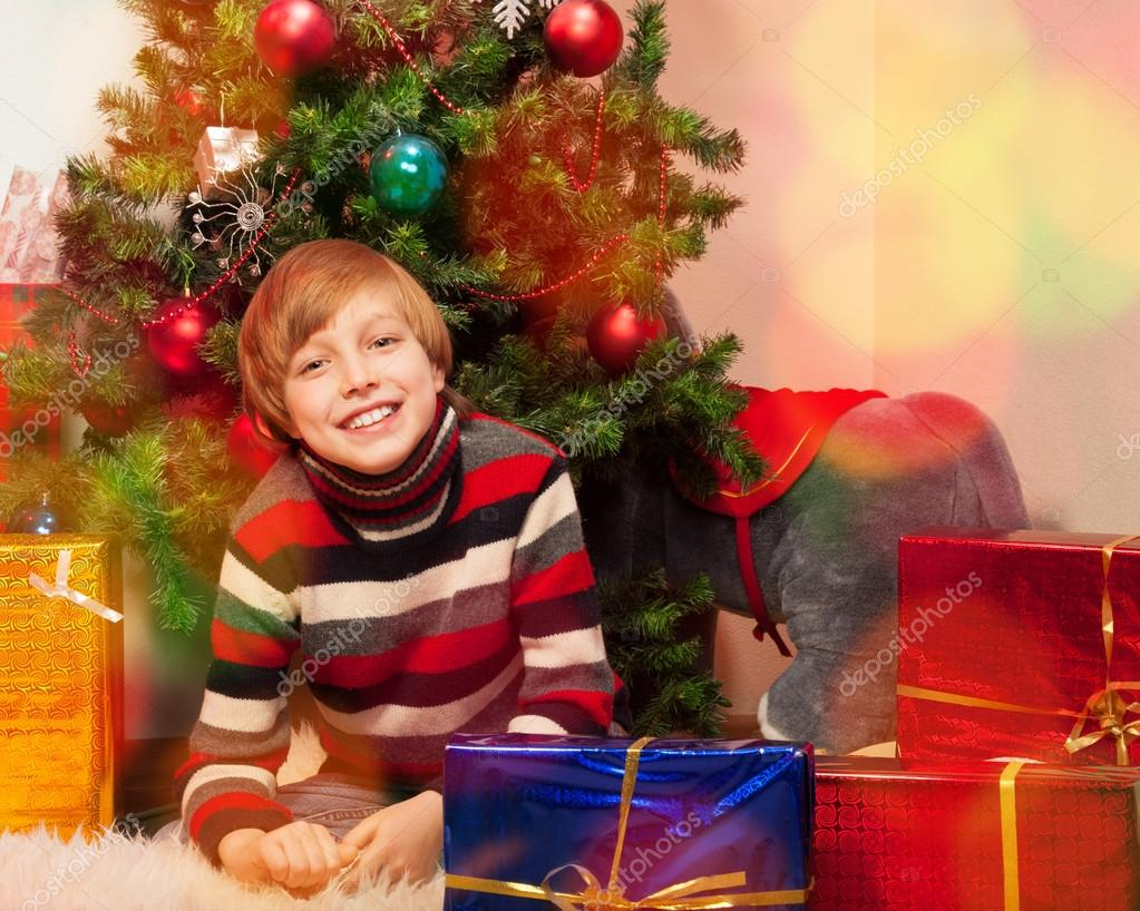 Cute little boy in New Year Eve waiting to open his presents  Stock Photo #16294987