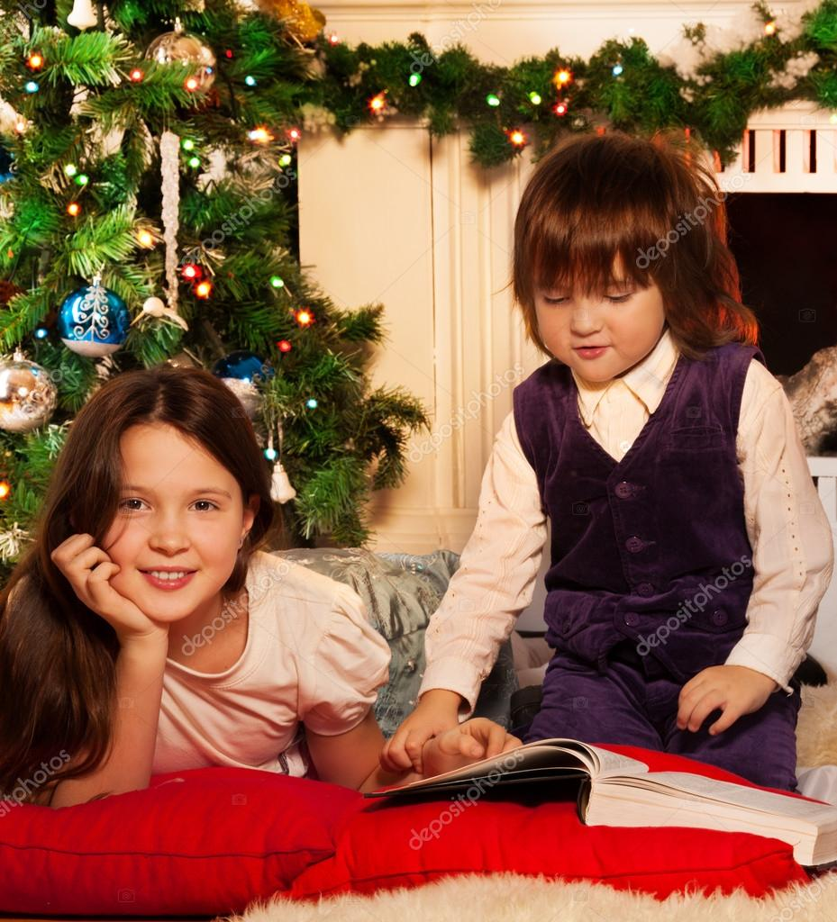 Two kids reading Christmas book sitting by the Christmas tree — Stock Photo #16295075