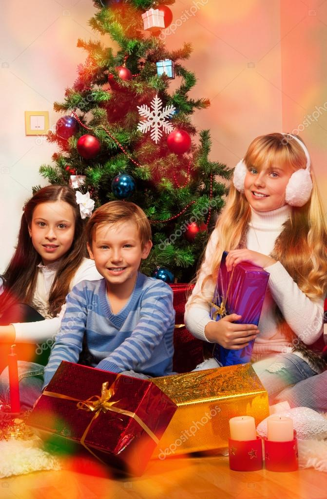 Three happy kids holding their present sitting near decorated tree  Photo #16295149